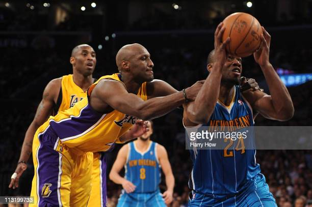 Carl Landry of the New Orleans Hornets is grabbed from behind by Lamar Odom of the Los Angeles Lakers in the fourth quarter in Game Five of the...