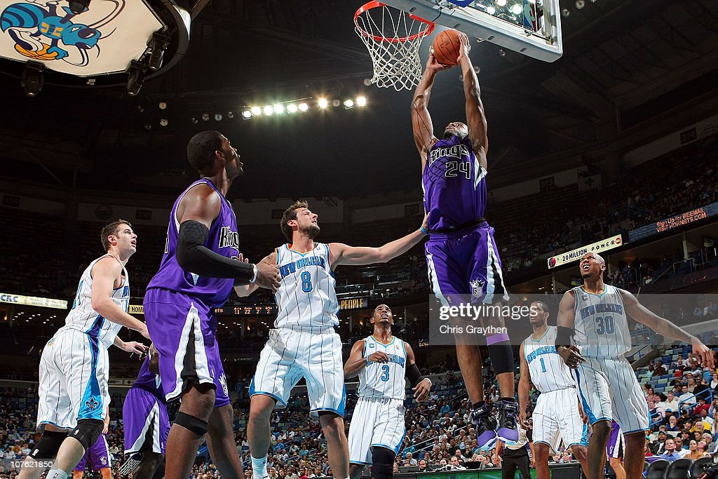 Carl Landry of the Sacramento Kings dunks the ball over Marco Belinelli of the New Orleans Hornets at the New Orleans Arena on December 15 2010 in...