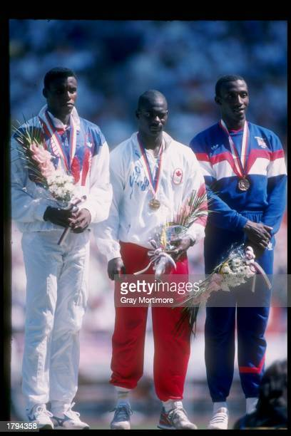 Carl Lewis of the United States stands with Ben Johnson of Canada and Linford Christie of Great Britain after completion of the 100 meter final at...