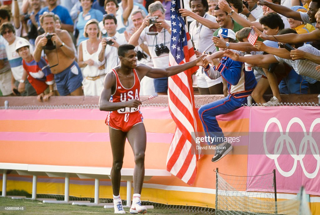 Carl Lewis #915 of the USA celebrates his victory in the Men's 100m race of the Track and Field competition of the 1984 Olympic Games held on August 4, 1984 in the Los Angeles Coliseum in Los Angeles, California. Photo by David Madison/Getty Images)