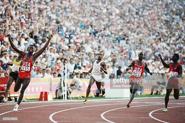 Carl Lewis of the USA raises his arms aloft as he crosses the line to win the 100 metres final from Sam Graddy of the USA # 126 Ben Johnson of Canada...