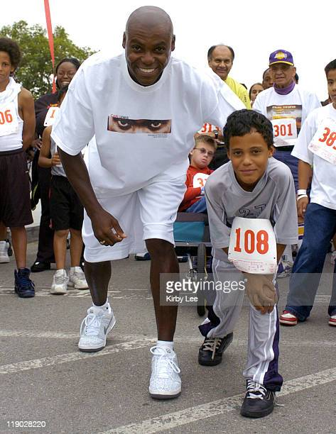 Carl Lewis poses with a male youth participant in the 5K run at the Carl Lewis International Track Field Camp and Festival at the Home Depot Center...