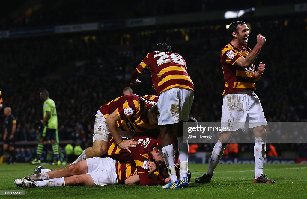 Carl McHugh of Bradford City (grounded) celebrates with team mates after scoring their third goal during the Capital One Cup Semi-Final 1st Leg match between Bradford City and Aston Villa at Coral Windows Stadium, Valley Parade on January 8, 2013 in Bradford, England.