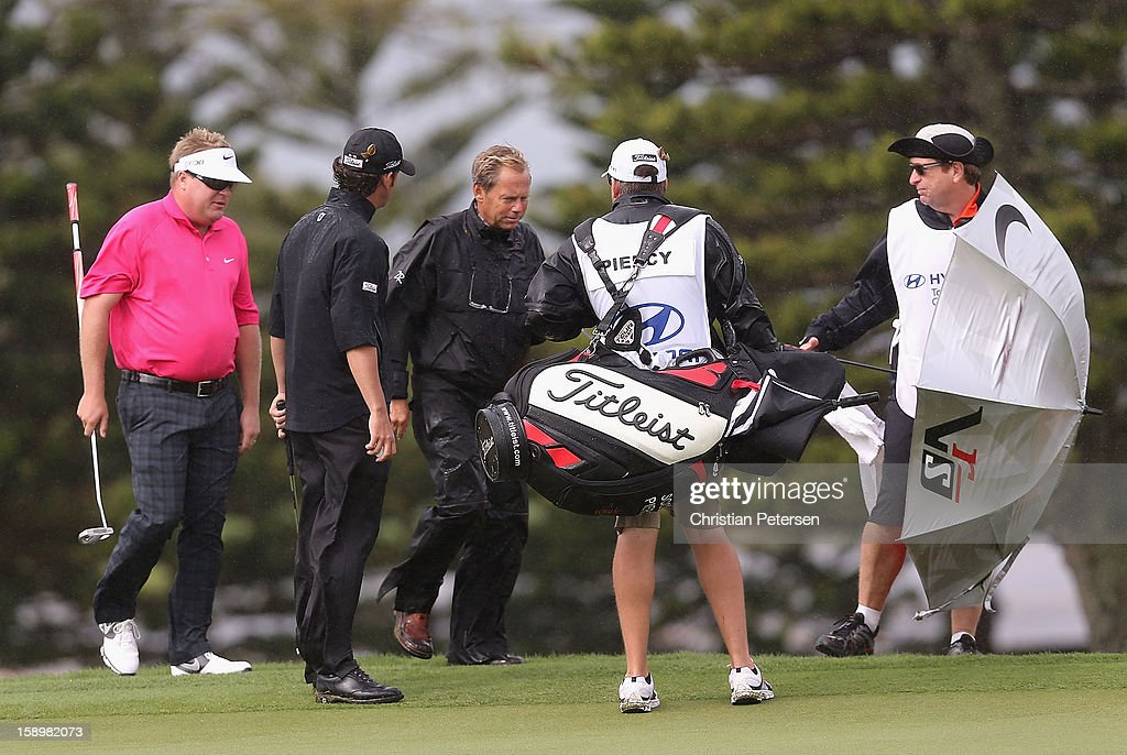 Carl Pettersson (L) of Sweden and Scott Piercy (2nd from left) talk with an official on the second hole green about the weather conditions during the first round of the Hyundai Tournament of Champions at the Plantation Course on January 4, 2013 in Kapalua, Hawaii.