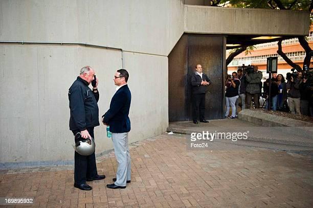 Carl Pistorius brother of Oscar Pistorius talks to Ampie Louw the paralympian's coach outside the Pretoria Magistrates court on June 4 in Pretoria...