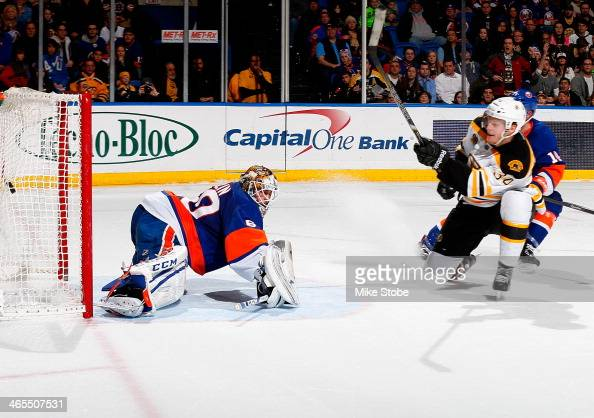 Carl Soderberg of the Boston Bruins puts the puck past Kevin Poulin of the New York Islanders for a goal at Nassau Veterans Memorial Coliseum on...