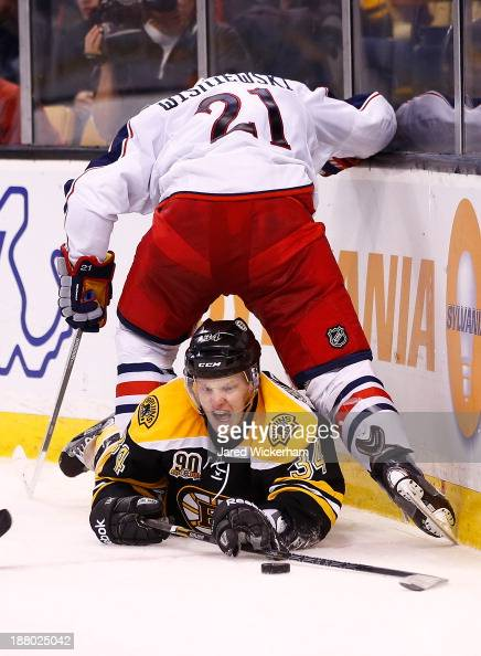 Carl Soderberg of the Boston Bruins reacher for a puck underneath the legs of James Wisniewski of the Columbus Blue Jackets in the third period...