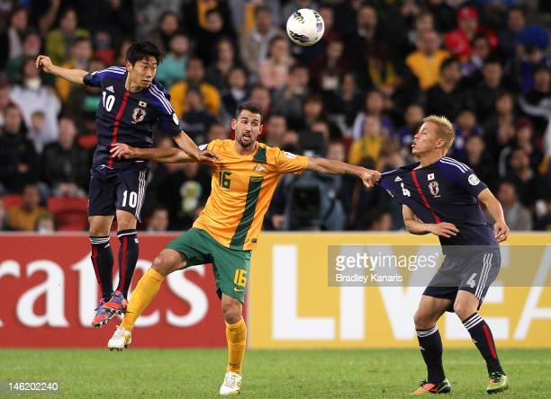 Carl Valeri of Australia competes for the ball against Keisuke Honda and Shinji Kagawa of Japan during the FIFA World Cup Asian Qualifier match...
