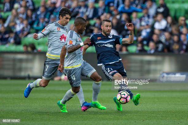 Carl Valeri of Melbourne Victory controls the ball in front of Roly Bonevacia of the Wellington Phoenix and Gui Finkler of the Wellington Phoenix...