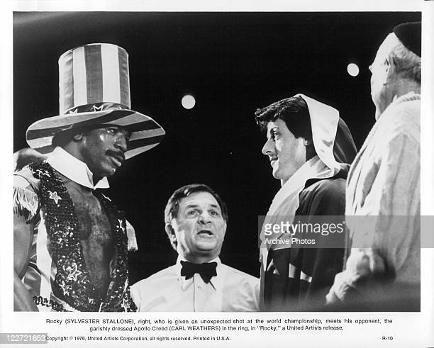 Carl Weathers wearing tall hat And Sylvester Stallone face each other standing in boxing ring in a scene from the film 'Rocky' 1976