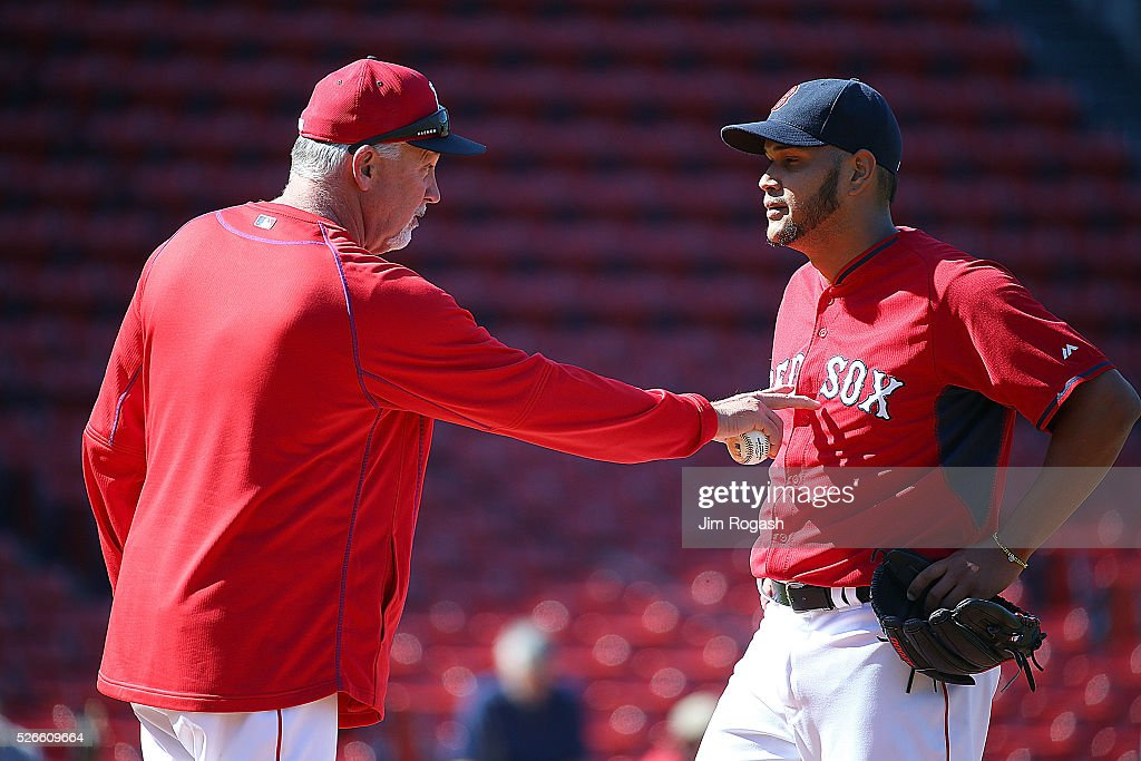 Carl Willis #54 of the Boston Red Sox offers advice to Eduardo Rodriguez #52 of the Boston Red Sox, who is on the DL, before a game the New York Yankees at Fenway Park on April 30, 2016 in Boston, Massachusetts.