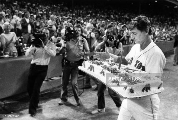 Carl Yastrzemski of the Boston Red Sox carries a birthday cake back to the dugout during a game against the Toronto Blue Jays at Fenway Park in...
