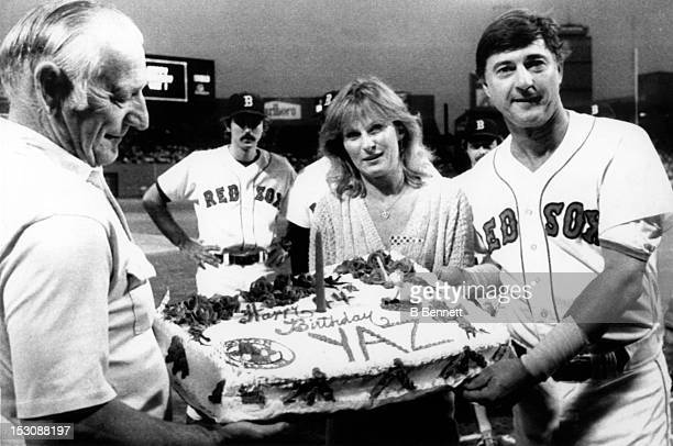 Carl Yastrzemski of the Boston Red Sox celebrates his 44th birthday with his daughter Marianne and father Carl Sr before their game against the...