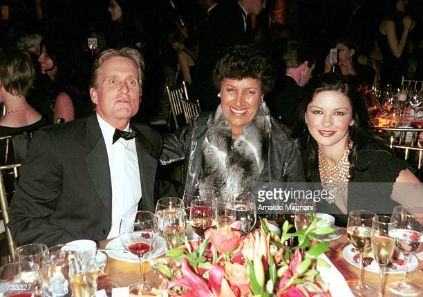 Carla Fendi president of Fendi sits in between actress Catherine Zeta Jones right and her husband/actor Michael Douglas as they pose for the...