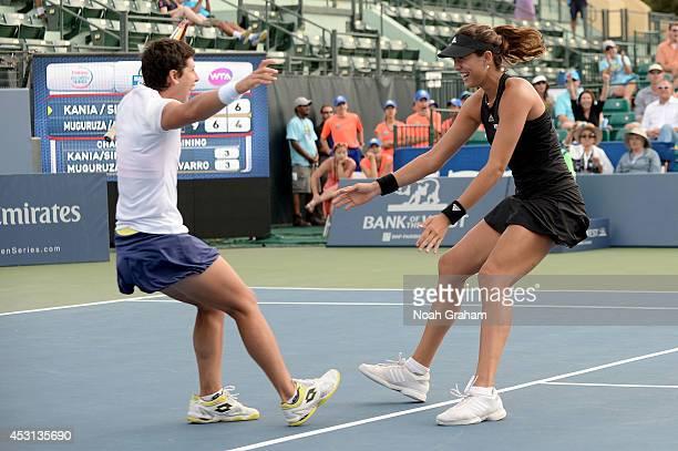 Carla Suarez Navarro and Garbine Muguruza of Spain celebrate after they defeated Paula Kania of Poland and Katerina Siniakova of the Czech Republic...