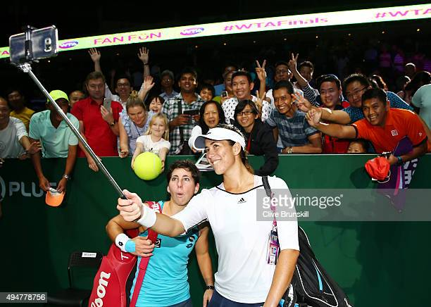 Carla Suarez Navarro and Garbine Muguruza of Spain take a selfie with fans after defeating HaoChing Chan and YungJan Chan of Chinese Taipei in a...