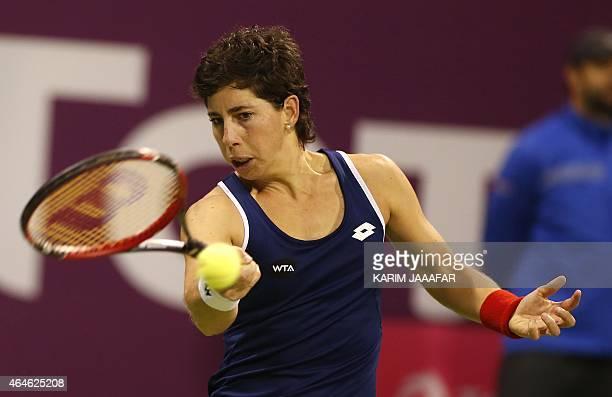 Carla Suarez Navarro of Spain returns the ball to Lucie Safarova of the Czech Republic during their WTA Qatar Open semifinal tennis match on February...