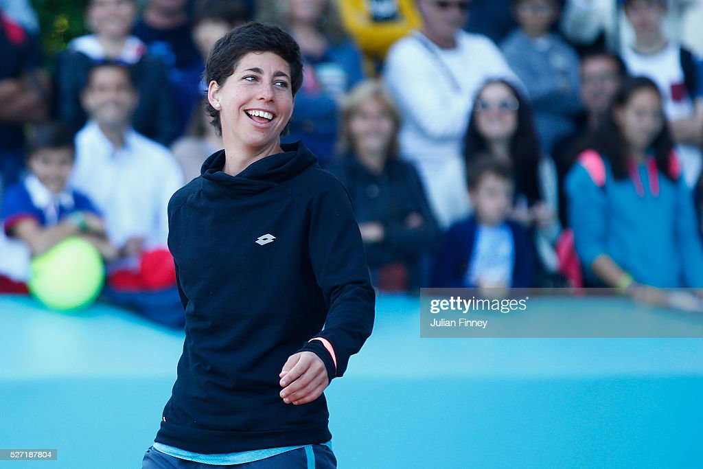 Carla Suarez Navarro of Spain smiles as she hits with sponsors during day three of the Mutua Madrid Open tennis tournament at the Caja Magica on May 02, 2016 in Madrid, Spain.