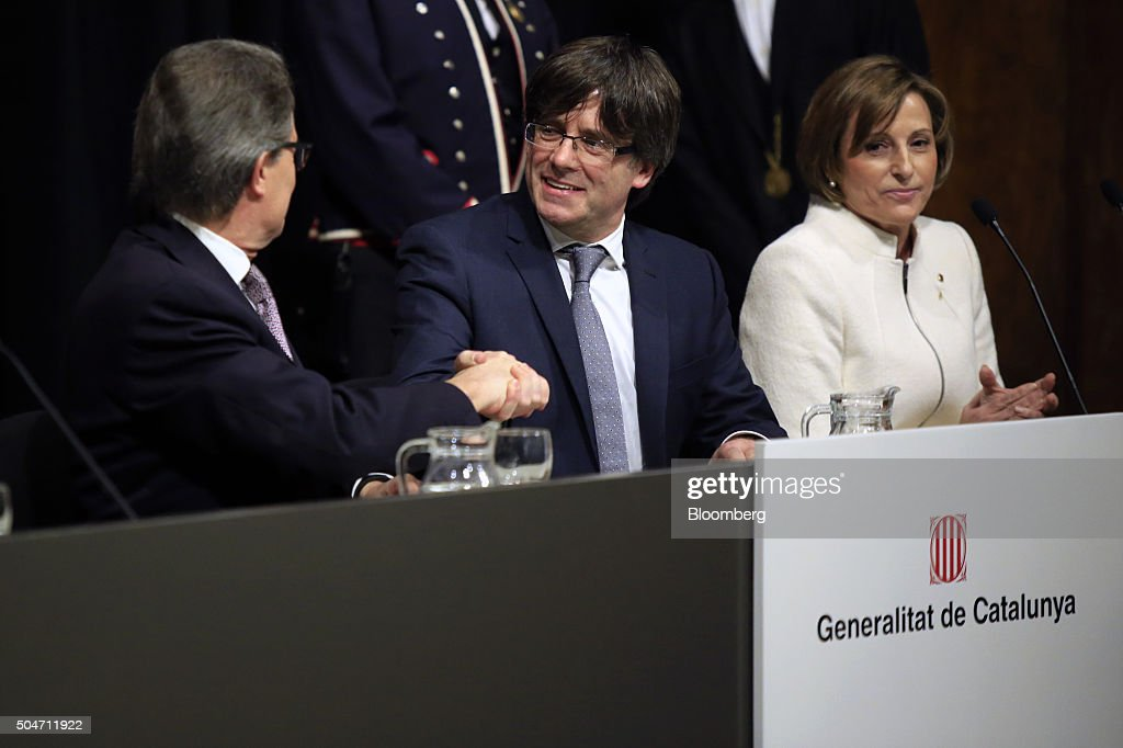 Carles Puigdemont, Catalonia's incoming president, center, shakes hands with Artur Mas, former Catalan acting president, left, as Carme Forcadell, Catalan Parliament president, looks on during the swearing in ceremony at the Palau de la Generalitat in Barcelona, Spain, on Tuesday, Jan. 12, 2016. The former mayor of Girona, a city near Spain's border with France, emerged as a last-minute compromise candidate as the fighting between two factions within the independence movement threatened to force new elections, jeopardizing their majority in the regional assembly. Photographer: Pau Barrena/Bloomberg via Getty Images