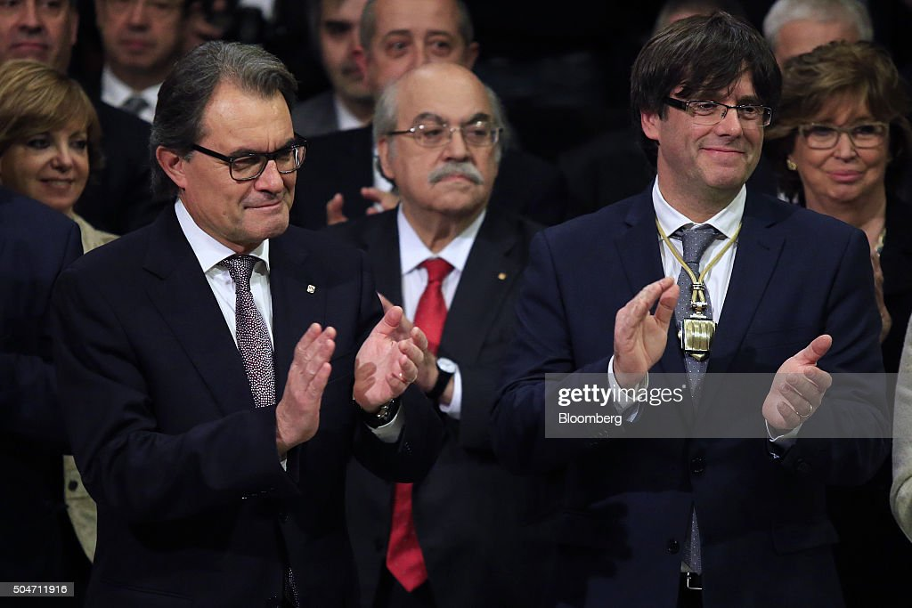 Carles Puigdemont, Catalonia's incoming president, right, and Artur Mas, former Catalan acting president, left, applaud during the swearing in ceremony at the Palau de la Generalitat in Barcelona, Spain, on Tuesday, Jan. 12, 2016. The former mayor of Girona, a city near Spain's border with France, emerged as a last-minute compromise candidate as the fighting between two factions within the independence movement threatened to force new elections, jeopardizing their majority in the regional assembly. Photographer: Pau Barrena/Bloomberg via Getty Images