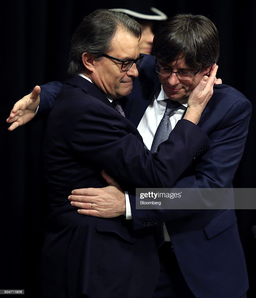 Carles Puigdemont, Catalonia's incoming president, right, embraces Artur Mas, former Catalan acting president, after he is sworn into office at the Palau de la Generalitat in Barcelona, Spain, on Tuesday, Jan. 12, 2016. The former mayor of Girona, a city near Spain's border with France, emerged as a last-minute compromise candidate as the fighting between two factions within the independence movement threatened to force new elections, jeopardizing their majority in the regional assembly. Photographer: Pau Barrena/Bloomberg via Getty Images