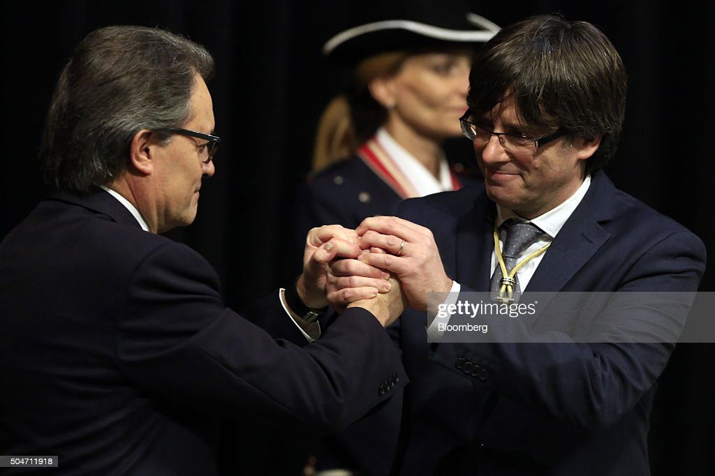 Carles Puigdemont, Catalonia's incoming president, right, shakes hands with Artur Mas, former Catalan acting president, during the swearing in ceremony at the Palau de la Generalitat in Barcelona, Spain, on Tuesday, Jan. 12, 2016. The former mayor of Girona, a city near Spain's border with France, emerged as a last-minute compromise candidate as the fighting between two factions within the independence movement threatened to force new elections, jeopardizing their majority in the regional assembly. Photographer: Pau Barrena/Bloomberg via Getty Images