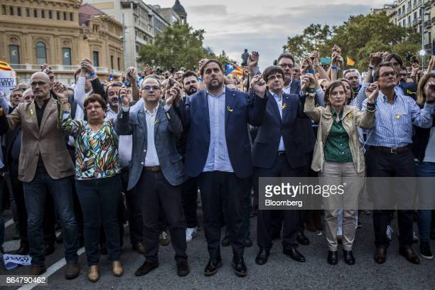 Carles Puigdemont Catalonia's president center right applauds during a demonstration against the Spanish government and the imprisonment of...