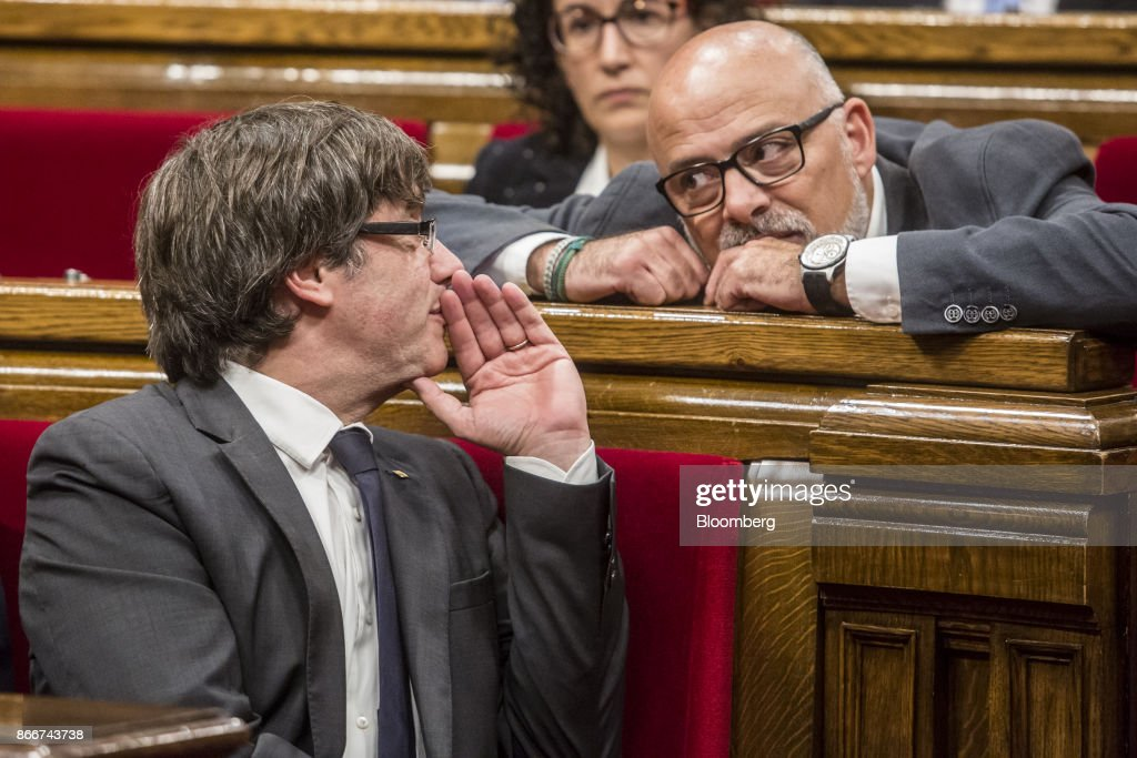 Carles Puigdemont, Catalonia's president, left, speaks with Lluis Corominas, spokesman of Junts Pel Si or 'Together for Yes' party, during a parliament session in Barcelona, Spain, on Thursday, Oct. 26, 2017. Puigdemont says he won't call a regional election that could have defused tension with Spain. Photographer: Angel Garcia/Bloomberg via Getty Images