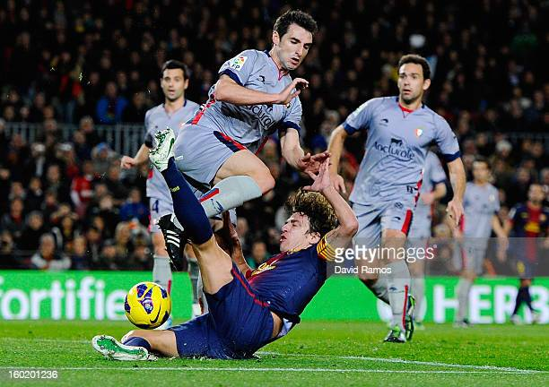 Carles Puyol of FC Barcelona duels for the ball with Marc Bertran of CA Osasuna during the La Liga match between FC Barcelona and CA Osasuna at Camp...