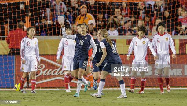 Carli Lloyd of the United States celebrates her score with Heather O'Reilly as dejected China team looks on in the second half at BBVA Compass...