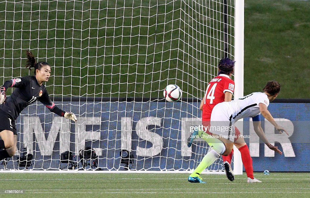 Carli Lloyd of the United States heads the ball past goalkeeper Wang Fei of China in the second half for her team's first goal in the FIFA Women's...