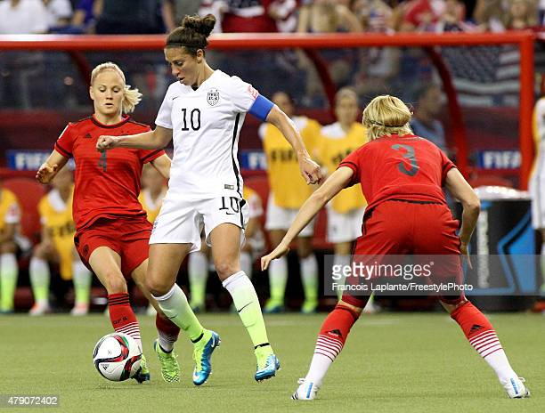 Carli Lloyd of the United States with the ball between Leonie Maier and Saskia Bartusiak of Germany in the first half in the FIFA Women's World Cup...