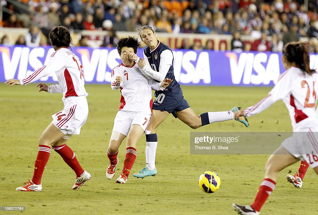Carli Lloyd #10 of the U.S. Women's National Team runs into Bi Yan midfielder #7 of the China Women's National Team in an international friendly game at BBVA Compass Stadium on December 12, 2012 in Houston, Texas. USA won 4 to 0.