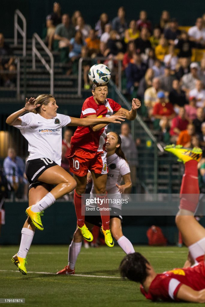 Carli Lloyd #10 of Western New York Flash wins an in the air challenge against Allie Long #10 of Portland thorns FC in the National Women's Soccer League Championship at Sahlen's Stadium August 31, 2013 in Rochester, New York.