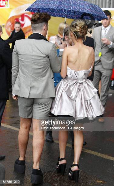 Carli Nuttall and her brother Jake shelter from the rain during day two of the 2012 John Smith's Grand National meeting at Aintree Racecourse...