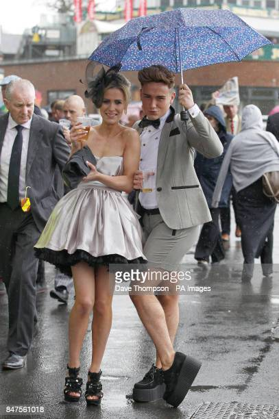 Carli Nuttall and her brother Jake shelter from the rain on the second day of the Aintree Grand National
