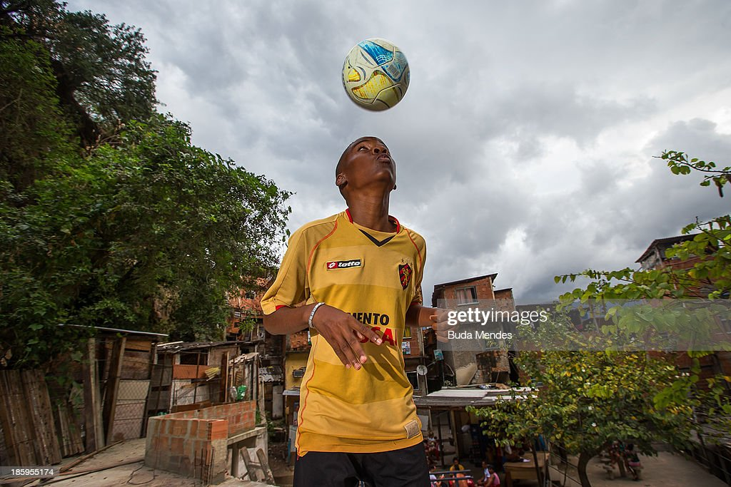 Carlinhos, athlete of Vila Nova Project, plays football on the rooftops in the Morro dos Macacos area on October 26, 2013 in Rio de Janeiro, Brazil. The Project Vila Nova was idealized by Alex Sandro and has so far run for 2 years, catering to children and young residents of the Morro dos Macacos area.