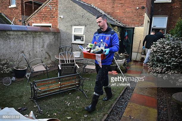 Carlisle United football player Michael Raynes helps people in Warwick road clear processions as they return to their properties after Storm Desmond...