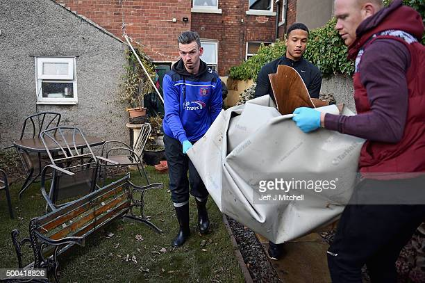 Carlisle United football players help residents in Warwick road clear processions as they return to their properties after Storm Desmond caused...