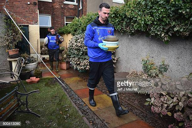 Carlisle United football players Michael Raynes and Luke Joyce help people in Warwick road clear processions as they return to their properties after...