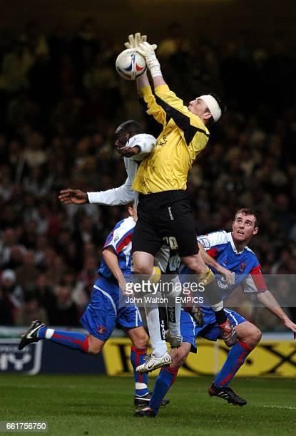 Carlisle United's goalkeeper Kieren Westwood claims the ball under pressure from Swansea City's Adebayo Akinfenwa
