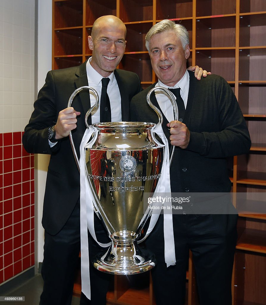 Carlo Ancelotti (R) and Zinedine Zidane of Real Madrid lifts the Champions League trophy during the UEFA Champions League Final between Real Madrid and Atletico de Madrid at Estadio da Luz on May 24, 2014 in Lisbon, Portugal.
