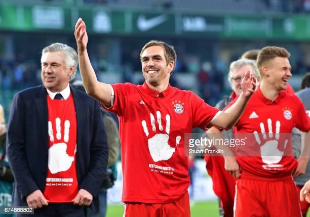 Carlo Ancelotti head coach of Muenchen and Philipp Lahm of Muenchen celebrate winning the Bundesliga title after the Bundesliga match between VfL...