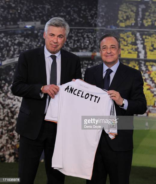 Carlo Ancelotti holds up a Real Madrid shirt as he stands alongside club president Florentino Perez while being presented as Real Madrid's new head...