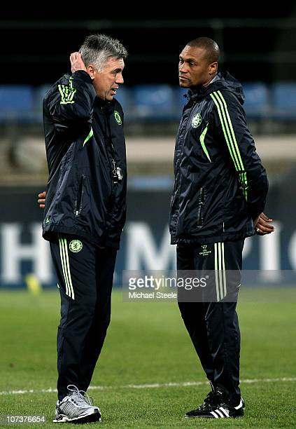 Carlo Ancelotti the Chelsea manager speaks with assistant coach Michael Emenalo during the Chelsea training session ahead of their UEFA Champions...
