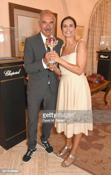 Carlo Capasa and Livia Firth pose with the Green Carpet Fashion Award as they attend an intimate lunch to announce Chopard as partner for The Green...