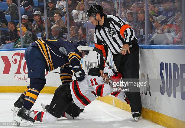 Carlo Colaiacovo of the Buffalo Sabres and Stephen Gionta of the New Jersey Devils collide with Referee Tom Kowal during an NHL game on October 24...