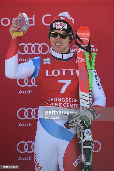 Carlo Janka of Switzerland holds his trophy on the podium after winning the 8th men's superG event at the FIS Alpine Ski World Cup in Jeongseon...
