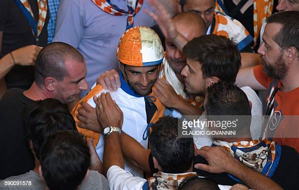 Carlo Sanna known as Brigante is greeted by people during the blessing of his horse Remistrio at the San Giovannino della Staffa church in Siena in...