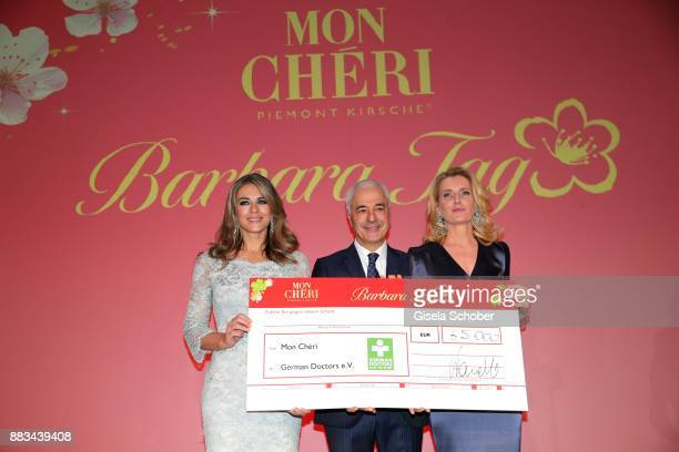 Carlo Vassallo Director Ferrero Germany Elizabeth 'Liz' Hurley and Dr Maria Furtwaengler with check during the Mon Cheri Barbara Tag at Postpalast on...